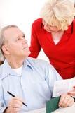 前辈:写比尔付款的资深夫妇 免版税图库摄影