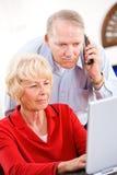 前辈:在电话的夫妇有技术支持 免版税库存照片