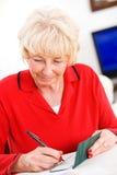 前辈:快乐地写支票的妇女 免版税库存图片