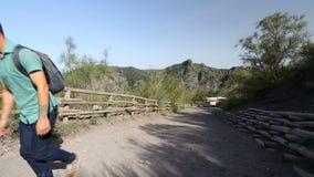 前进上升沿在山的地面路的年轻男性背包徒步旅行者在晴天 股票录像