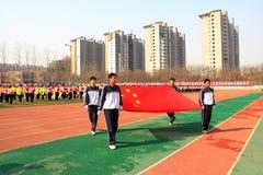 前进在操场的国旗伴游 免版税库存图片