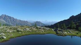 前进在清楚的蓝色湖和松木上在晴朗的夏日 欧洲意大利阿尔卑斯瓦尔d `奥斯塔室外绿色 股票录像