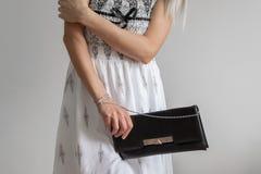 前面庄稼观点的年轻时髦的女人穿戴了与长的礼服并且拿着手袋 库存照片