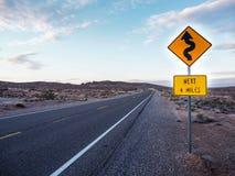 前面弯曲的标志警告 库存照片