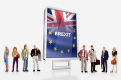 """前面的微型人†""""人与英国和欧盟旗子的一个广告牌为2016年公民投票结合了 免版税图库摄影"""