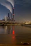 水前面的能源厂在与烟的夜之前在烟囱 库存照片