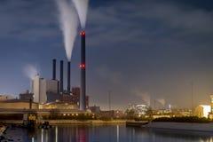 水前面的能源厂在夜之前在城市 免版税图库摄影