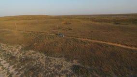 前面鸟瞰图:驾驶在乡下公路的一个干草原的大银色SUV 影视素材