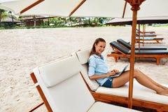 前餐馆常设夏天女服务员妇女工作年轻人 放松使用在海滩的计算机的妇女 自由职业者 库存照片