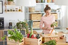 剥一棵红萝卜的妇女在厨房里 免版税库存照片