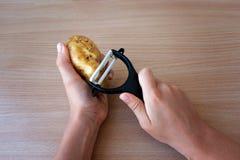 剥与黑削皮器的手土豆 免版税库存图片
