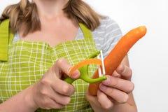 剥红萝卜的妇女使用食物削皮器 图库摄影