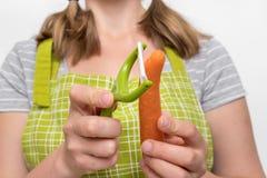 剥红萝卜的妇女使用食物削皮器 库存图片