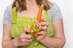 剥红萝卜的妇女使用食物削皮器 免版税图库摄影