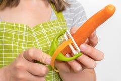 剥红萝卜的妇女使用食物削皮器 库存照片
