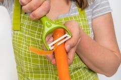 剥红萝卜的妇女使用食物削皮器 免版税库存照片