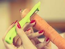 剥红萝卜菜的妇女 免版税库存图片