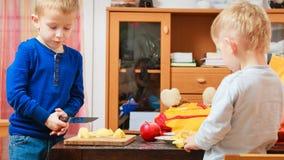 剥苹果和吃的两个男孩 库存照片
