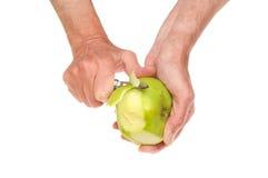 剥苹果的手 免版税库存照片
