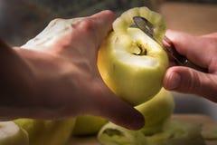 剥落皮肤绿色苹果的女性手使用一把削皮刀 免版税库存图片