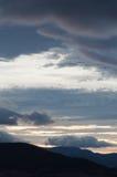 剧烈的云彩和天空在日落或日出期间 免版税库存图片