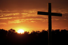 剧烈的天空桔子覆盖明亮的Yelllow太阳大基督徒十字架 免版税库存照片