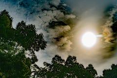 剧烈的太阳通过黑暗的天空发出光线,与过滤器 库存照片