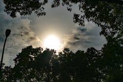 剧烈的太阳通过黑暗的天空发出光线,与过滤器 图库摄影