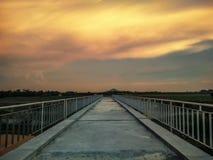 剧烈的日落云彩在桥梁结束时 免版税图库摄影