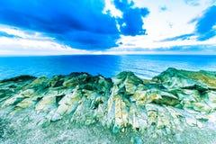 剧烈的日落通过在海洋的多云黑暗的天空发出光线 免版税库存照片