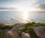 剧烈的日落通过在海洋的多云黑暗的天空发出光线 免版税图库摄影
