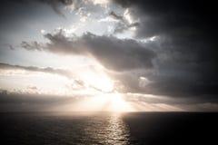 剧烈的日落通过在海洋的多云黑暗的天空发出光线 图库摄影