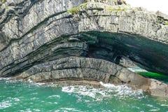 剧烈的沿海峭壁岩石分层堆积曲线,形成在小野鸭水色海浪的洞在循环入口半岛,克莱尔郡,爱尔兰 库存照片