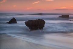 剧烈的海景模糊的波浪 在日落期间的石头 免版税图库摄影