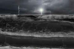 剧烈的海洋,与闪电灯塔的黑暗的多云天空为 库存图片