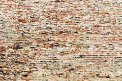 剩余水泥和灰色油漆部分盖的老和被风化的脏的红砖墙壁 库存照片