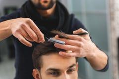 剪人发的纯熟理发师 免版税库存图片