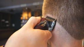 剪他的有电剃刀的客户的头发的发式专家的手在理发店 做男性的美发师的胳膊 股票视频