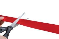剪刀切开红色丝带或磁带 背景查出的白色 免版税库存照片