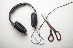 剪刀切开从耳机的导线和因而停止非常大声的非法被盗版的音乐 库存照片