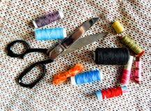 剪刀和五颜六色的缝合针线 免版税库存照片
