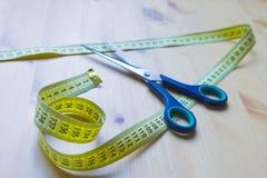 剪刀和厘米在一张木桌上 皇族释放例证