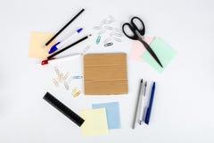 剪刀笔铅笔贴纸纸夹和纸板在桌上说谎 在视图之上 库存图片