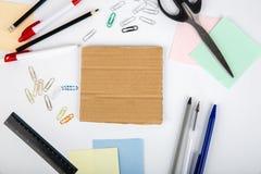剪刀笔铅笔贴纸纸夹和纸板在桌上说谎 在视图之上 免版税库存照片