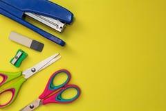 在黄色背景的学校辅助部件 剪刀,笔,磨削器,订书机 r 免版税图库摄影