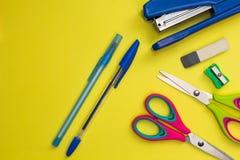 在黄色背景的学校辅助部件 剪刀,笔,磨削器,订书机 图库摄影