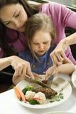 剪切女儿食物帮助的妈妈 库存照片