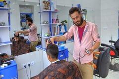 剪十几岁的男孩在理发店里面的伊朗美发师` s头发 免版税库存照片