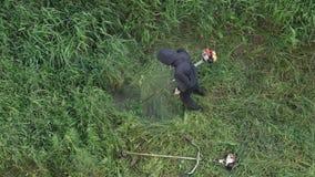 剪在庭院手工汽油草坪整理者的花匠草 股票视频