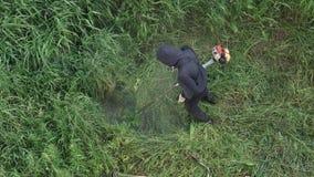 剪在庭院手工汽油草坪整理者的花匠草 ?? 股票录像